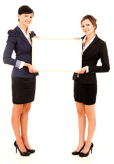 two young business women holding the whiteboard
