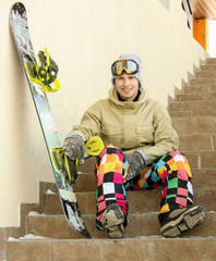 Snowboarder sitting on a ladder