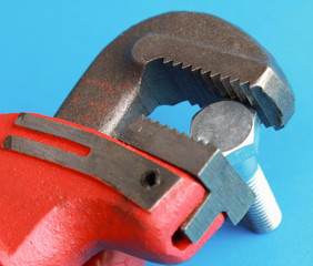Closeup of adjustable wrench over blue