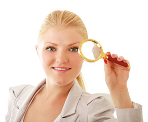 Young attractive businesswoman looking into a magnifying glass