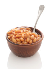 Cooked beans with red sauce in a clay bowl