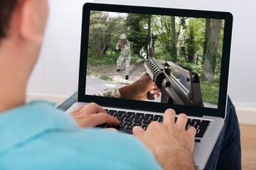 Man Playing Action Game On Laptop
