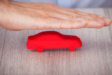 Hand Covering Red Car Model
