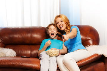 Happy mother pointing at TV and son laughing