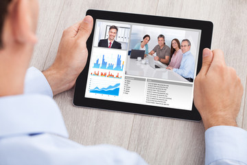 Businessman Video Conferencing With Team On Digital Tablet