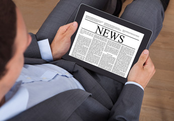 Businessman Reading News On Digital Tablet In Office