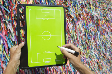 Hands Writing on Football Tactics Board Wish Ribbons Brazil