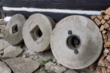 Old millstones leaning on the wooden wall of the house