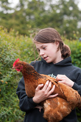 Young girl hugging a hen