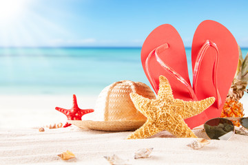 Summer beach with straw hat, seashells and sandals