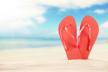 Summer beach with red sandals in sand