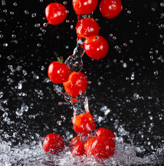 Cherry tomato in water splash on black background