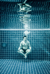 Man under water in a swimming pool to relax in the lotus positio