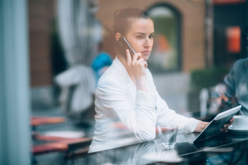 Serious businesswoman talking on phone in coffee shop