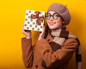 Redhead girl with gift box on yellow background.