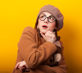 Redhead girl in coat and scarf on yellow background.