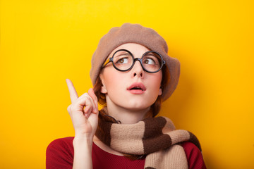 Redhead girl in glasses and scarf on yellow background.