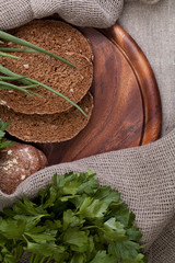 Black bread on a wooden board with herbs