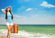 Young brunette girl with suitcase on the beach in summer time.