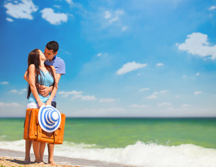 Young couple with suitcase on the beach in summer day.