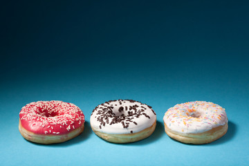 three donuts with color icing isolated on blue background with c