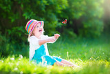 Beautiful toddler girl playing with butterfly - Fine Art prints