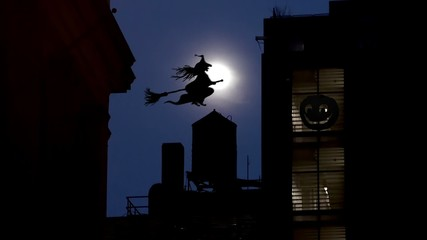 Witch on a broom is flying over New York. Halloween.
