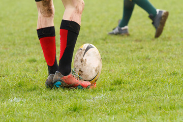 Dirty legs about to kick a rugby ball