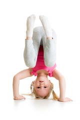 kid girl standing head over heels and smiling, isolated on white