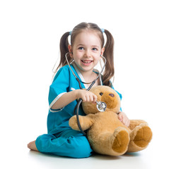 Adorable child with clothes of doctor examining teddy bear toy o