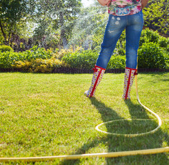 Woman holding garden water hose watering garden