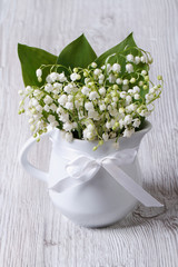 Beautiful bouquet of lilies of the valley in a white jug