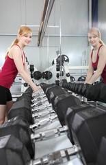 Frau im Fitnessstudio greift nach Hanteln - mit Spiegelbild