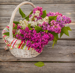 Basket with lilac twigs on a wooden table