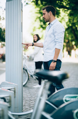 Young man renting bicycle at bike share docking station