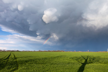 Mammatus clouds and a rainbow above a green land with road and s