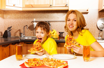 Hungry boy and his mother eating pizza in kitchen