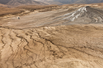 Person walking on mud volcanoes