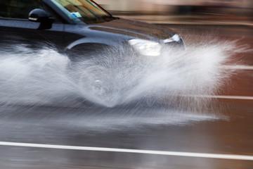 fahrendes Auto auf regennasser Straße