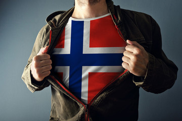 Man stretching jacket to reveal shirt with Norway flag