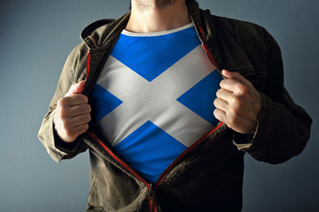 Man stretching jacket to reveal shirt with Scotland flag
