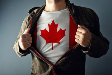 Man stretching jacket to reveal shirt with Canada flag