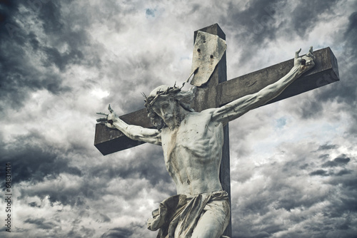 Crucifixion. Christian cross with Jesus Christ statue over storm - 64831414