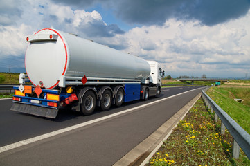 A tanker truck on the highway leading through the countryside