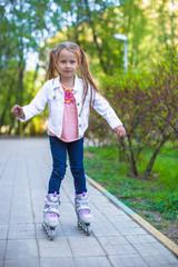 Adorable little girl on roller skates in the park