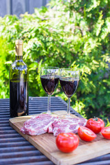 Bottle of red wine, steak and tomatoes on barbecue outdoors