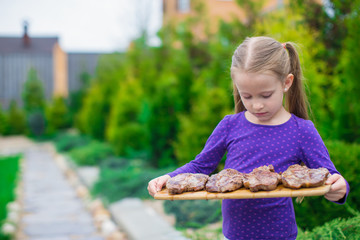 Adorable little girl with grilled steaks in the hands outdoor