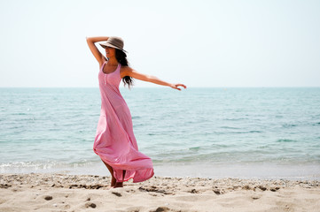 Beautiful woman with long pink dress and sun hat on a tropical b