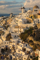White city on slope of a hill at sunset, Oia, Santorini, Greece