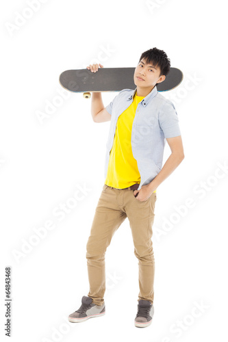 confident young man standing and holding a skateboard